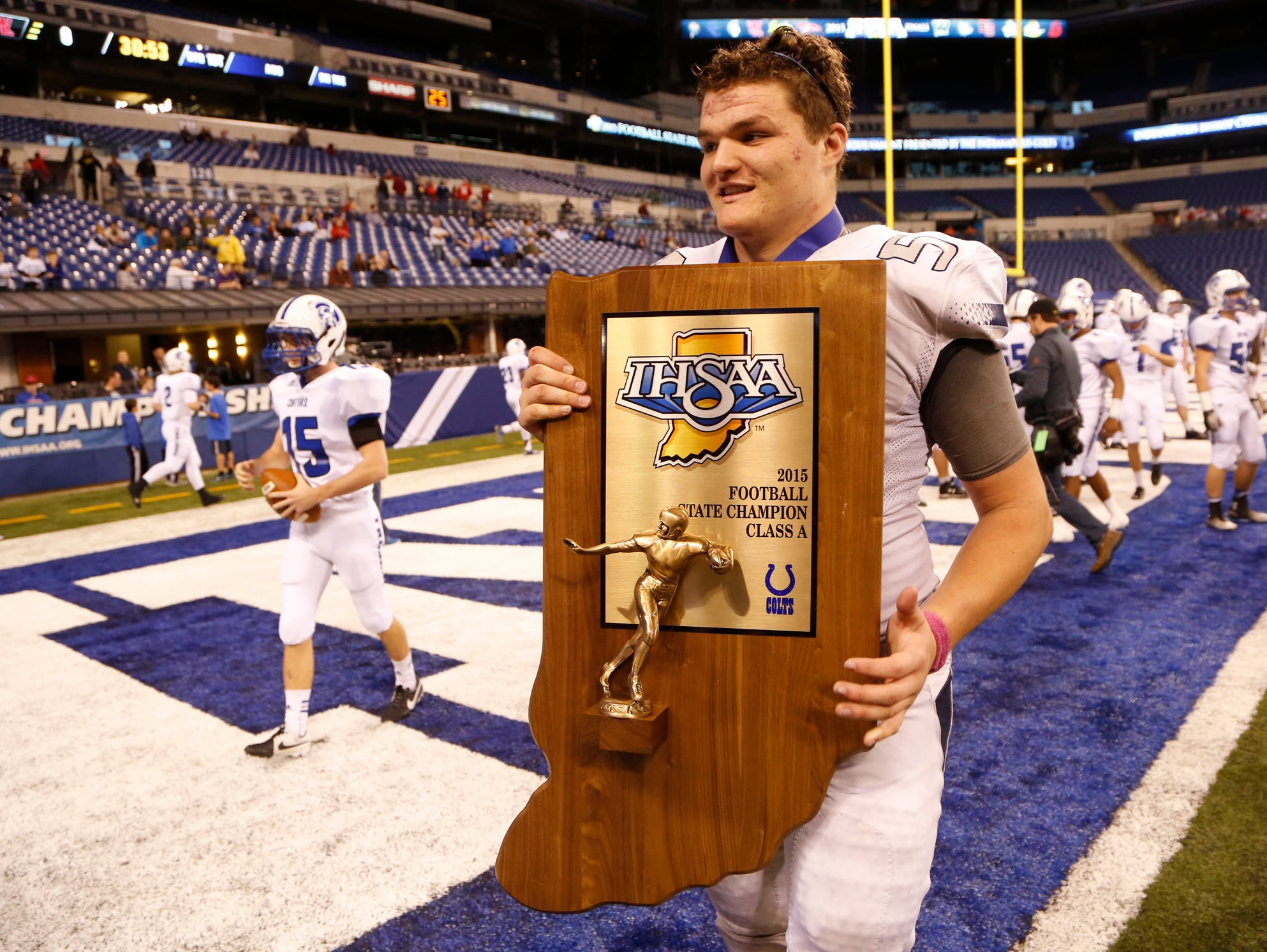 Coy Cronk carries the Class A state title trophy off the field after Central Catholic defeated Linton-Stockton 34-7 in the Class A state finals Friday, November 27, 2015, at Lucas Oil Stadium in Indianapolis.