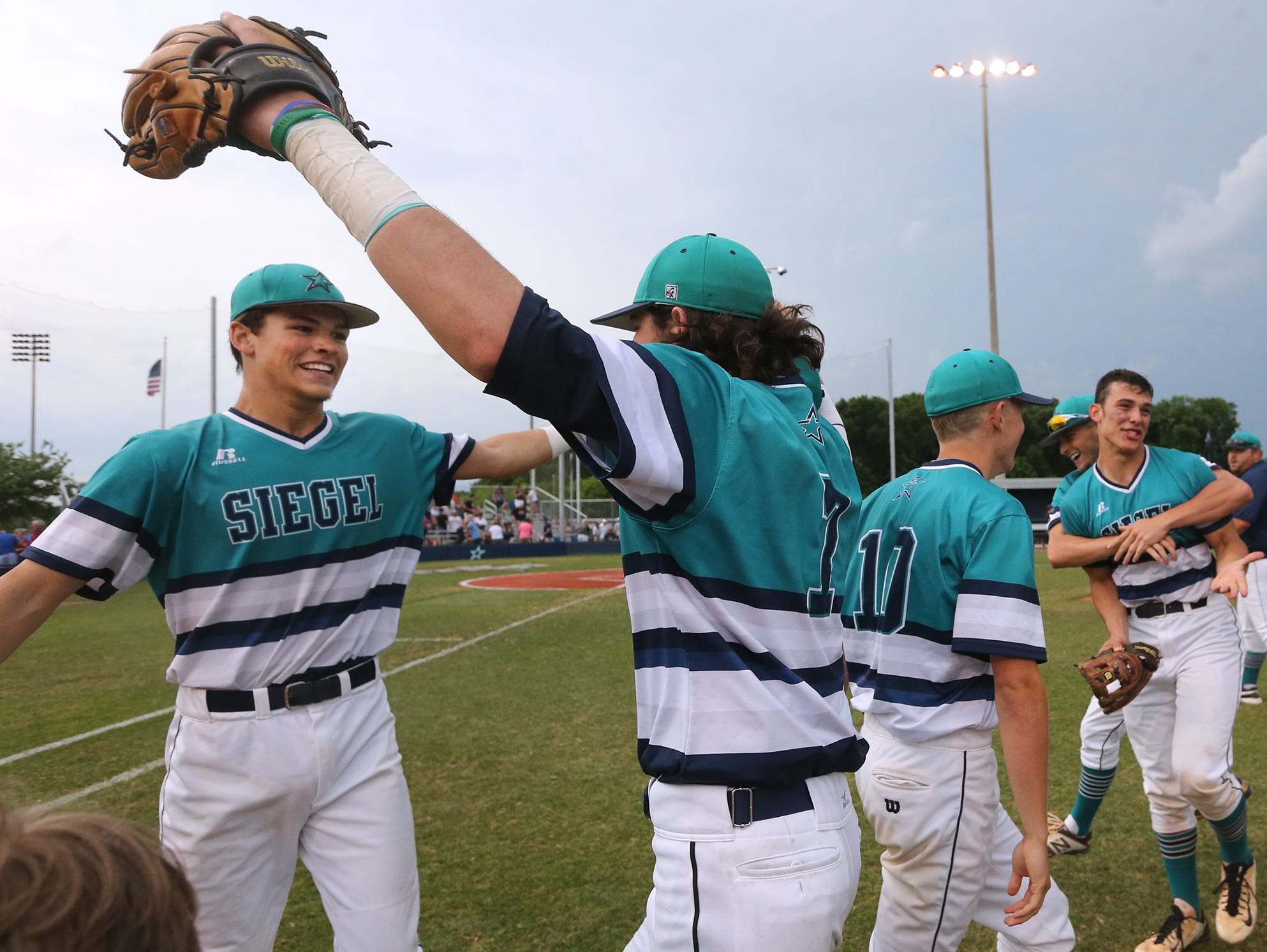 Siegel's Drew Benefiedl (24) and teammate Jordan Middleton (7) begin to hug after winning two games in a row to advance to the state championship game.