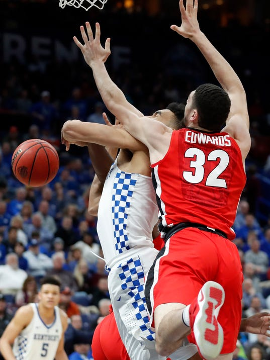 Kentucky's Sacha Killeya-Jones, left, is fouled on his way to the basket by Georgia's Mike Edwards, right, during the second half of an NCAA college basketball quarterfinal game at the Southeastern Conference tournament Friday, March 9, 2018, in St. Louis. Kentucky won 62-49. (AP Photo/Jeff Roberson)