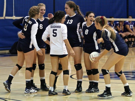 La Quinta's players celebrate a point during the second set of an away match with Shadow Hills High School on Sept. 15, 2015.