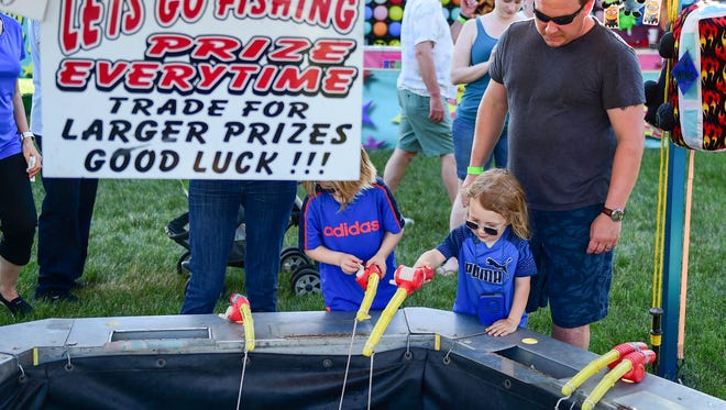 Kids go fishing on the midway during the 2016 Green Days carnival at Johnston Public Library.