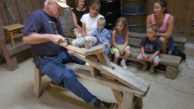 Farmer Frank explained an antique piece of woodworking equipment as visitors watch.