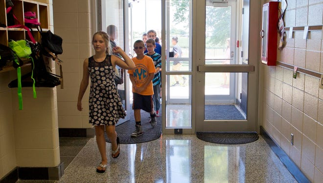 Students at Mintoyne Elementary head to a classroom on the first day back at the school for students and teachers Wednesday, August 13, 2014, near Romney. After a tornado struck the school on Nov. 17, 2013, students and staff were excited to be back.