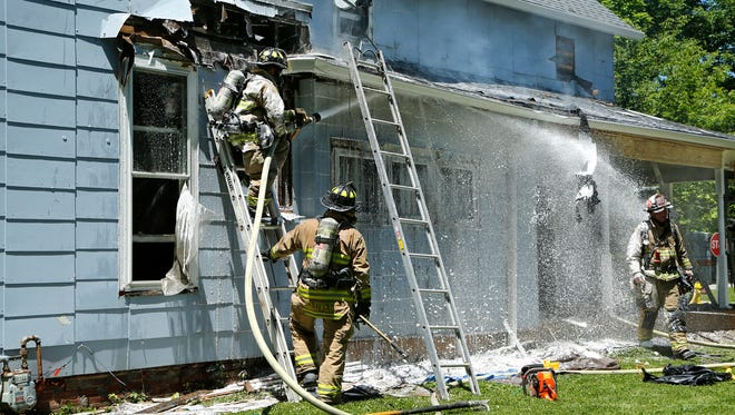 Firefighters bring a fire under control Friday afternoon at 103 E. Oak Street in West Lafayette. Homeowner Michael Poling said  he was removing paint with a heat gun when the fire started. There were no injuries.