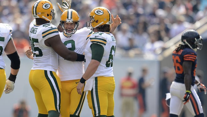 Green Bay Packers kicker Mason Crosby (2) is congratulated by teammates Datone Jones (95) and Brett Goode (61) after Crosby hit a 53-yard field goal in the third quarter during Sunday's game at Soldier Field in Chicago. Evan Siegle/Press-Gazette Media/@PGevansiegle