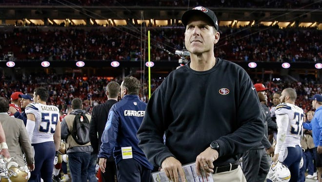 Head coach Jim Harbaugh of the San Francisco 49ers runs off the field after the 49ers lose 38-35 in overtime to the San Diego Chargers at Levi's Stadium on December 20, 2014 in Santa Clara, California.