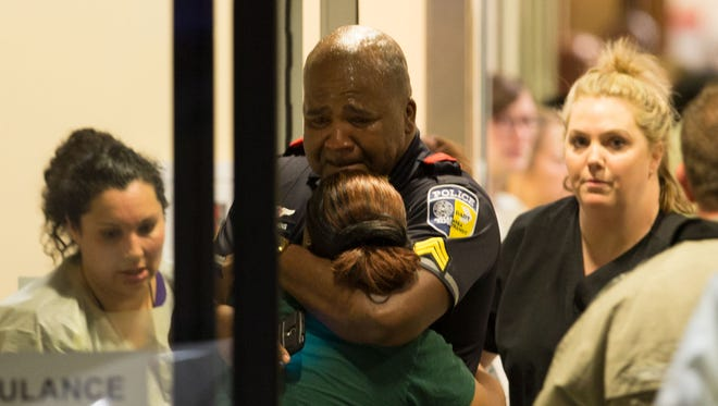 A Dallas Area Rapid Transit police officer receives comfort at the Baylor University Hospital emergency room entrance Thursday, July 7, 2016, in Dallas.