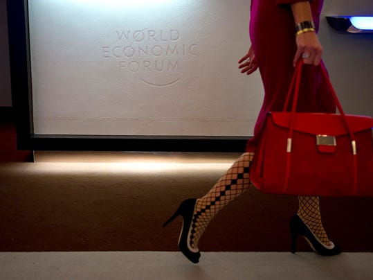 A woman passes the logo of WEF on the se