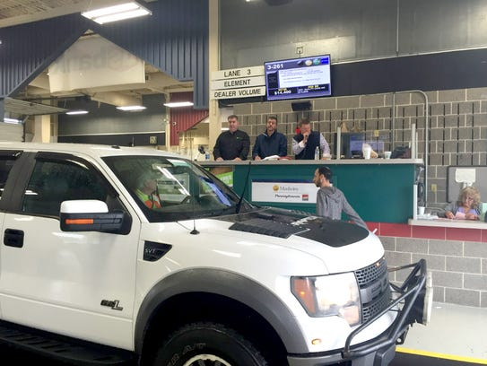 Auctioneers at Manheim Auto Auction take bids on a