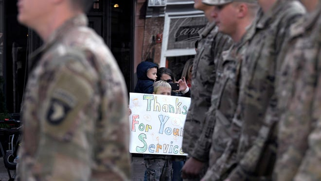 Davis Gleason,7, holds a sign of thanks as Fort Campbell soldiers from D Company march by in the Franklin Veterans Day Parade in downtown Franklin on November 10, 2017.