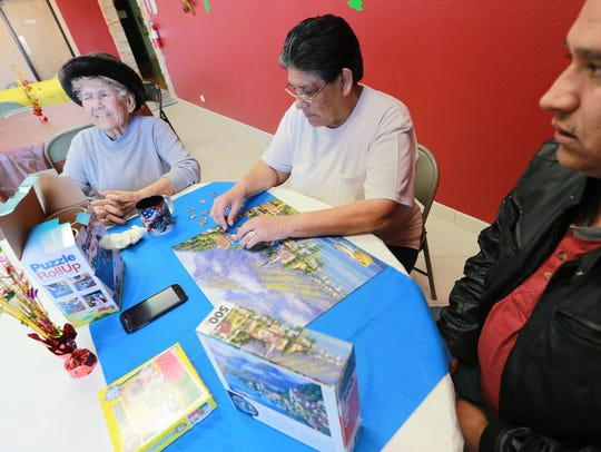 Carmen Chavez, center, works on a puzzle while accompanied