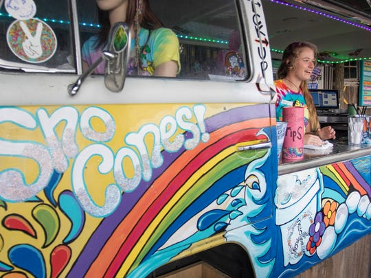 Annabelle Owens chats while cleaning the counter at the Sno Cones! stand set up outside of Flounders Chowder House in Pensacola Beach, FL on Thursday, June 16, 2016.  Beach leaders are consider ing parking lot food trucks.