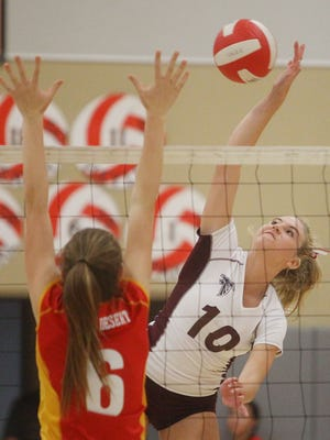 At right, La Quinta High School's Baylie Dashner goes for a spike as Palm Desert High School's Danielle Boss tries to defend during their game at Palm Desert High School.