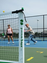 Norman Levy and Iris Boreman (left), coordinators of  Bergen County Parks Pickleballer Club, give Bill Ervolino (right) a lesson in Pickleball at Overpeck Park in Leonia on Wednesday July 02, 2017.