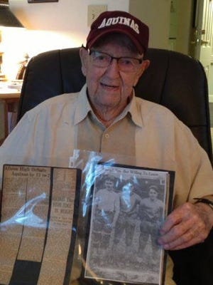 Peter Tierney, who was 100 at the time, shows off old clippings from Aquinas' inaugural football season in 1930. Mr. Tierney died on Sunday at age 104. He was the school's oldest living alum.