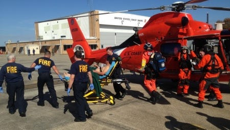 Members of the Coast Guard transport four people after saving them from a life raft. The victims boarded the life raft after a vessel fire southwest of Grand Isle Monday.