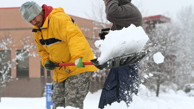 Men shovel sidewalks in Hillsborough Saturday, after about 6 inches of snow fell overnight. Another storm is on the way.