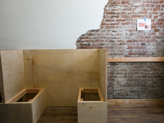The inside of soon-to-open burger bar Bo & Vine is seen Friday, April 21, on Liberty Street in downtown Salem. Small booths line the room, and original brick can be seen peeking from behind the restaurant's white walls.