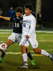 Catholic Central senior Logan Trevorrow (right) and Cranbrook Kingswood's Tony Yazbeck come together on the pitch during the Catholic League title game Wednesday at Bishop Foley.