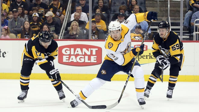 Predators left wing Filip Forsberg (9) moves the puck between Penguins right wing Bryan Rust (17) and center Jake Guentzel (59) during the first period Oct 7, 2017.