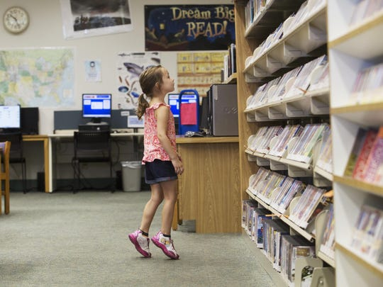 Evie Harper, 4, tries to get a better view while checking out the selection of DVDs for children at the Bonita Springs Public Library. Bonita Springs is scheduled to get a new library along with North Fort Myers.