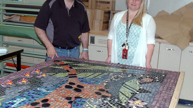 Parent Kevin Epling and MacDonald Middle School art teacher Lauren Engler with the mosaic created by MacDonald students. The jaguar is modeled after one drawn by Epling's son Matt in sixth grade.