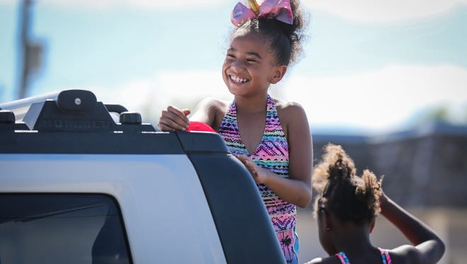 Kids smile at the crowds along the streets during the Juneteenth parade Saturday, June 16, 2018, along Martin Luther King Drive.