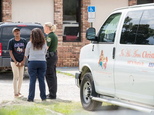 Day care worker Louvenia Shantae Johnson, left, talks with investigators following the death of a child at the In His Arms Christian Academy in Pensacola on Friday, August 18, 2017.