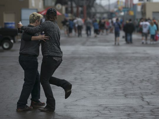 Carey Brubaker (left) and Susie Tourville  dance in a light rain at ISM Raceway at the Xfinity Series NASCAR race on  March 10, 2018, in Avondale.
