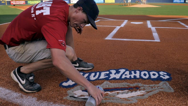 Pensacola Blue Wahoos game day grounds keeper Kaleb Lewis creates one of his custom designs for the Blue Wahoos field before the start of a recent game against the Mobile Bay Bears.