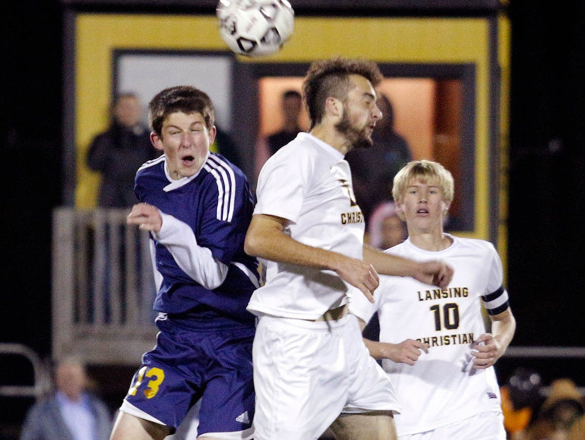 Lansing Christian's Alex McDowell, center, and Shrine Catholic's Ian Gappy, left, vie for a header as Lansing Christian's Jacob Lyon (10) watches Tuesday, Oct. 27, 2015, in Lansing, Mich.