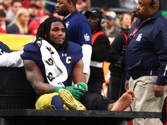 Notre Dame LB Jaylon Smith (9) cries as he is carted