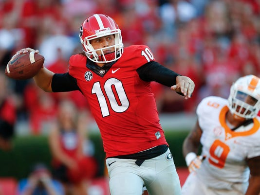 Georgia quarterback Jacob Eason (10) throws on the run as Tennessee defensive end Derek Barnett (9) gives chase in the second half of an NCAA college football game Saturday, Oct. 1, 2016, in Athens, Ga. Tennessee won 34-31. (AP Photo/John Bazemore)