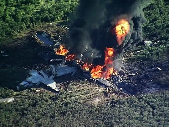 Smoke and flames rise from a KC-130T Marine tanker that crashed in a soybean field in Leflore County July 10, killing 16.