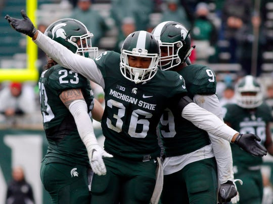 Michigan State's Arjen Colquhoun (36), Chris Frey (23) and Montae Nicholson celebrate a play during the fourth quarter against Purdue, Saturday, Oct. 3, 2015, in East Lansing.