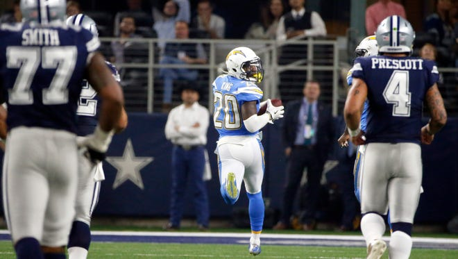 Dallas Cowboys' Tyron Smith (77) and quarterback Dak Prescott (4) watch as Los Angeles Chargers cornerback Desmond King (20) returns an interception for a touchdown in the second half of an NFL football game, Thursday, Nov. 23, 2017, in Arlington, Texas. (AP Photo/Michael Ainsworth)