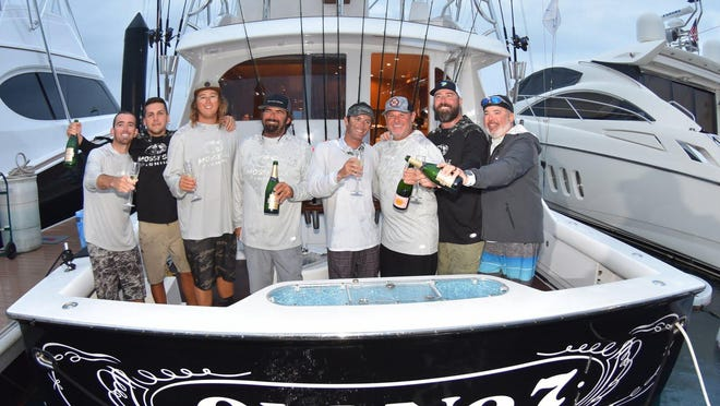 The captain and crew of the Old No. 7 celebrate their Top Boat victory in the 83rd Silver Sailfish Derby with a champagne toast.