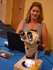 Pollution control manager Danette Kinaszczuk displays a sample of actual red tide organisms.