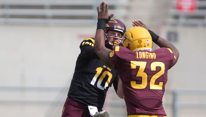 ASU's Taylor Kelly throws a pass over Antonio Longino in a scrimmage during ASU football spring practice at Sun Devil Stadium in Tempe, AZ on Saturday, April 12, 2014.