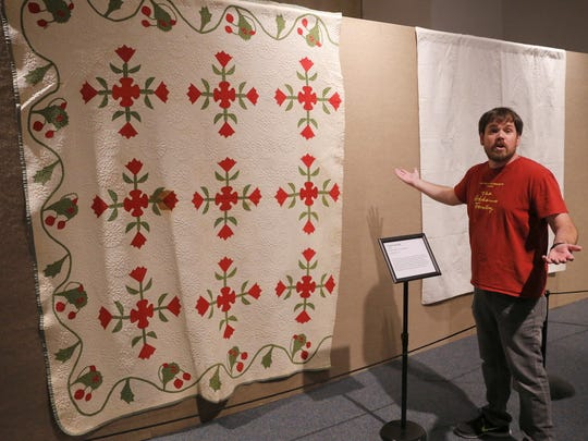 "Farmington Museum curator Jeffrey Richardson talks about a detail in one of the items featured in the ""Quilts and the Stories They Tell"" exhibition opening at the museum."