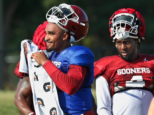 How will Oklahoma fare with quarterback Jalen Hurts, the onetime hero at Alabama? Hurts, left, and running back Trey Sermon take a breather during practice in Norman on Monday, Aug. 5, 2019. (AP Photo/Sue Ogrocki)