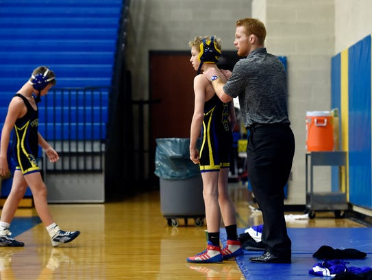 Chance Marsteller helps a wrestler warm up before his