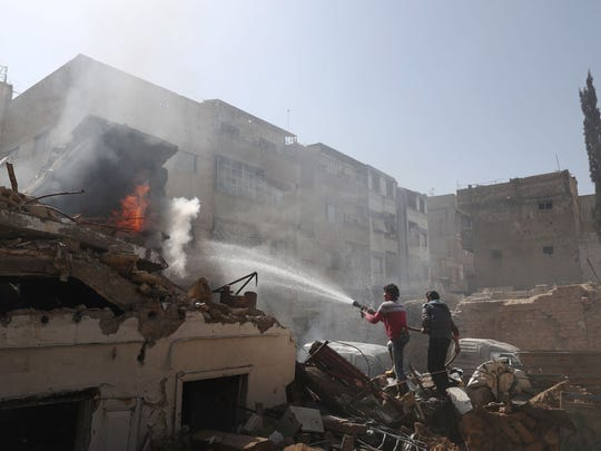 Syrian men and Civil Defence volunteers, also known as the White Helmets, extinguish fire following reported government airstrike on the rebel-held town of Douma, on the eastern outskirts of the capital Damascus, on Feb 26, 2017.
