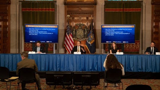 Gov. Andrew Cuomo relies on two television screens on the floor to see his PowerPoint presentations for his daily coronavirus briefings. Reporters and aides, meanwhile, are kept at a social distance