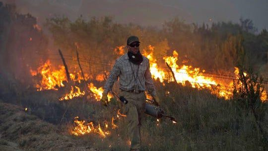 A firefighter works on the McDaniel Fire burning northwest of San Angelo on Saturday.