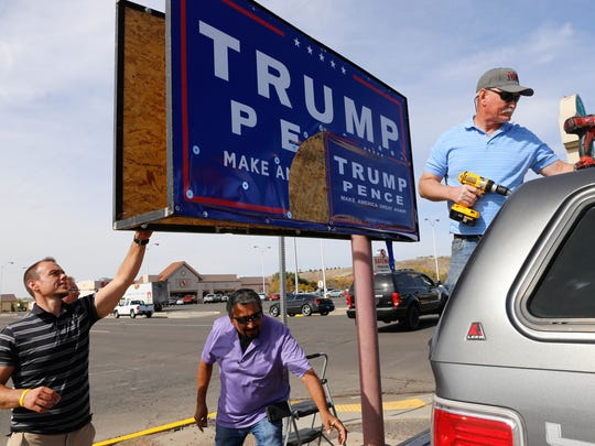 San Juan County Republican Party Chairman Sean Sharer, left, party member Hector Rangel and Treasurer Joe Roger repair a damaged campaign sign Thursday on West Main Street in Farmington.