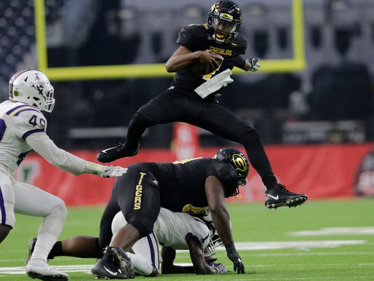 Grambling State quarterback Devante Kincade (1) leaps over Alcorn State defensive back Deago Sama (1) in the second quarter during the Southwestern Athletic Conference championship football game in Houston, Texas, Saturday, Dec. 2, 2017. (Tim Warner/Houston Chronicle via AP)