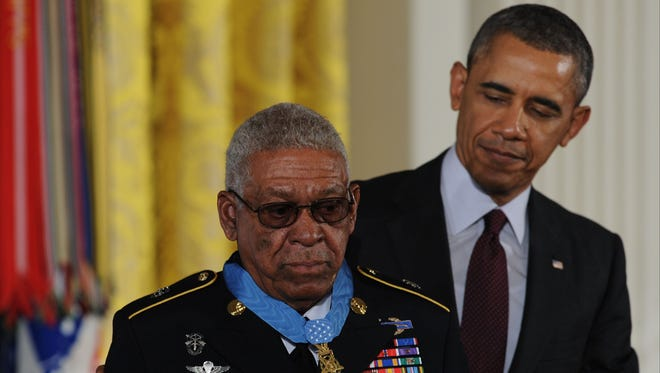 President Barack Obama awards the Medal of Honor to Melvin Morris in 2014 in the East Room of the White House.