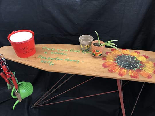 Portable garden work bench made from an antique ironing board.