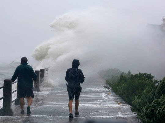 Pedestrians walk into huge waves crashing over The